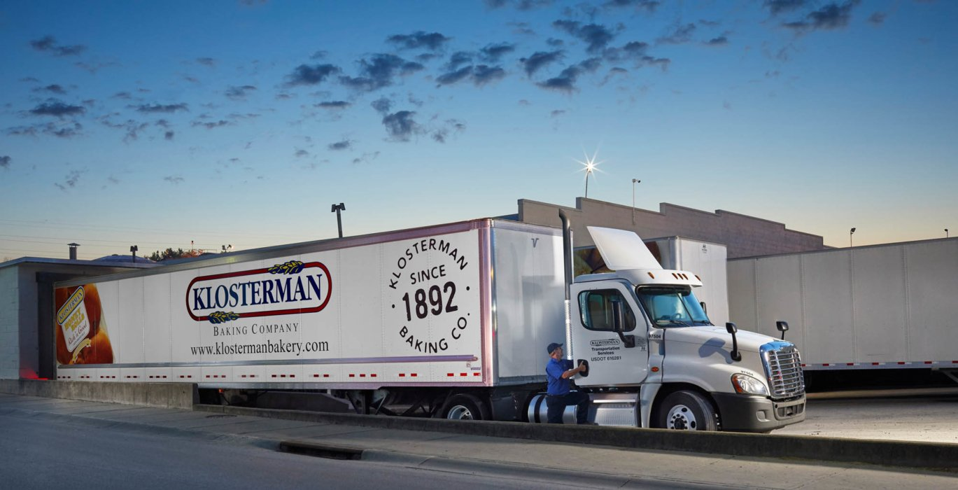 A truck driver getting in truck for klosterman baking company
