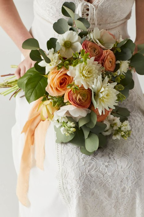 A close up of an orange and white flower bouquet on a woman's lap