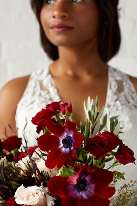 Close up of a woman in wedding dress holding a bouquet of red and pink flowers