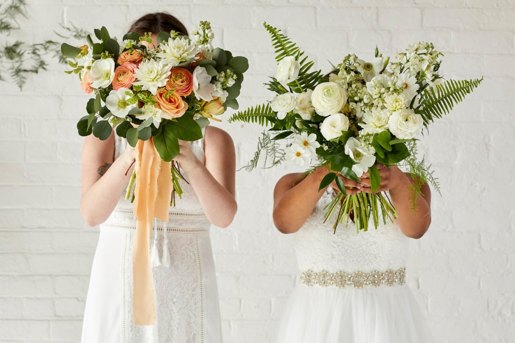 Two women in wedding dresses holding up flower bouquets over their faces
