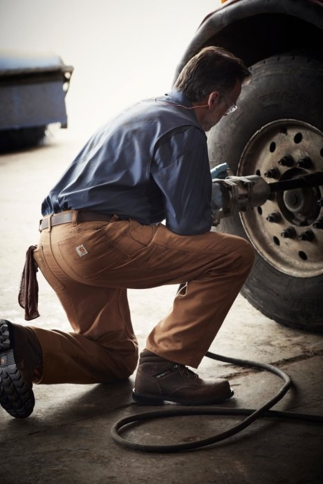 Man working in Carhartt clothes working on a truck tire while kneeling