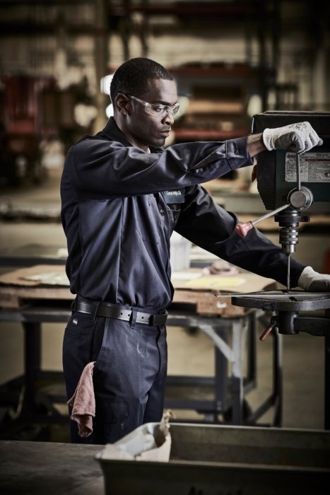 A worker wearing blue work apparel operating a drill press - industrial photography