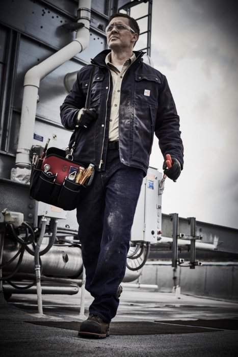 Man walking with work gear at an industrial site,