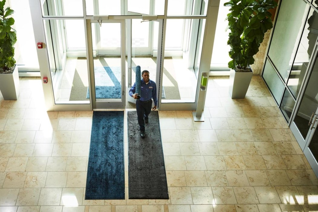 A working walking in the entrance lobby with mats
