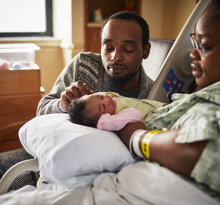 A new mother and father looking at their newborn in a hospital | Healthcare Photographer