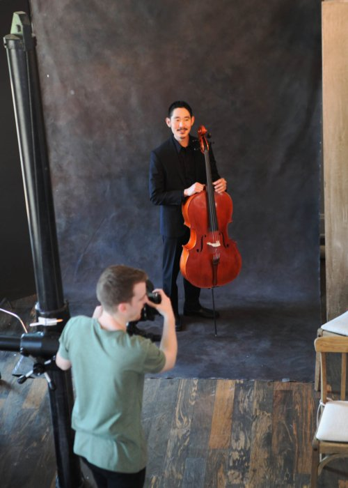 Jake Anderson taking a portrait of a man with a cello - concert nova