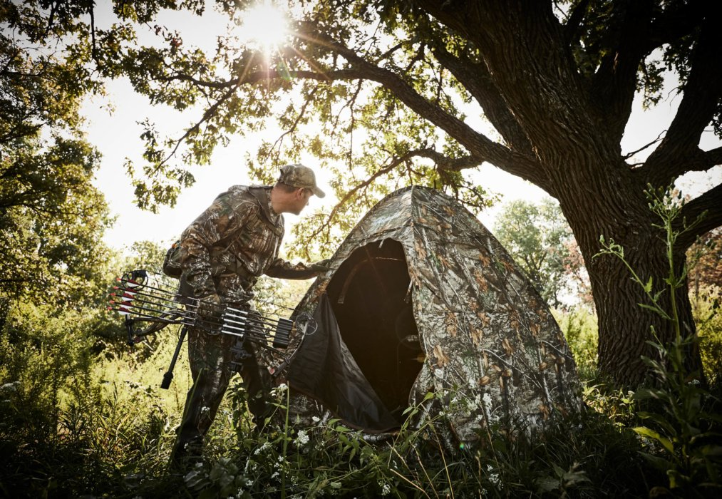 A hunter going into his tent under a tree - outdoor hunting photography