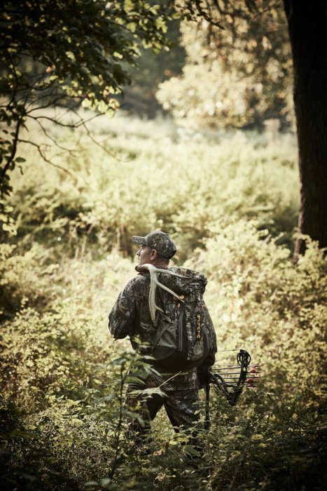 A hunter walking through tall grasses - outdoor photography