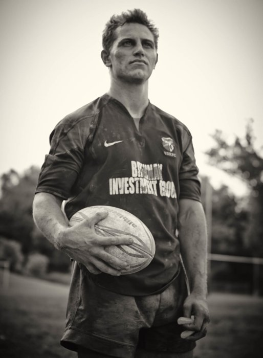 Athlete portrait of a young rugby player holding rugby ball