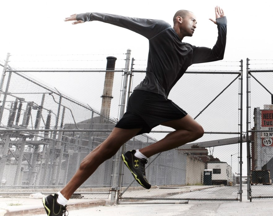 An athlete running with athletic apparel in front of a industrial setting