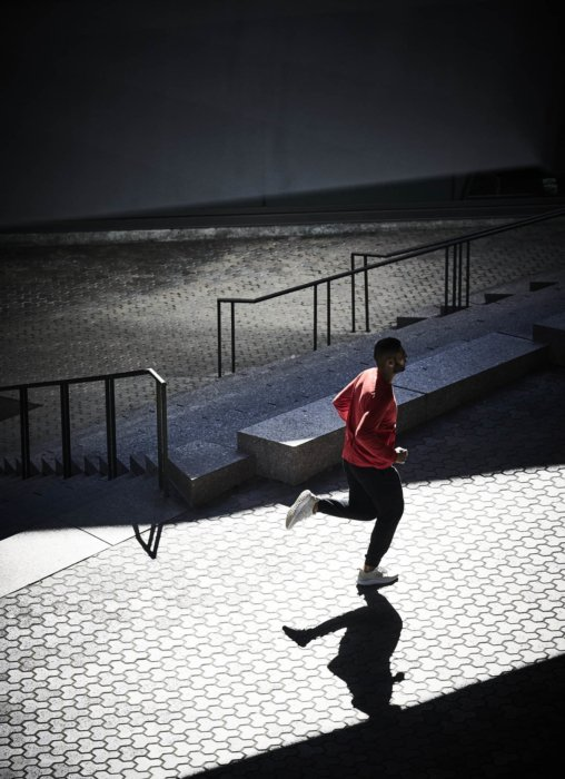 A young runner running in a modern university campus