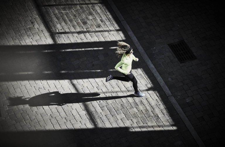 A runner going across a open concrete campus