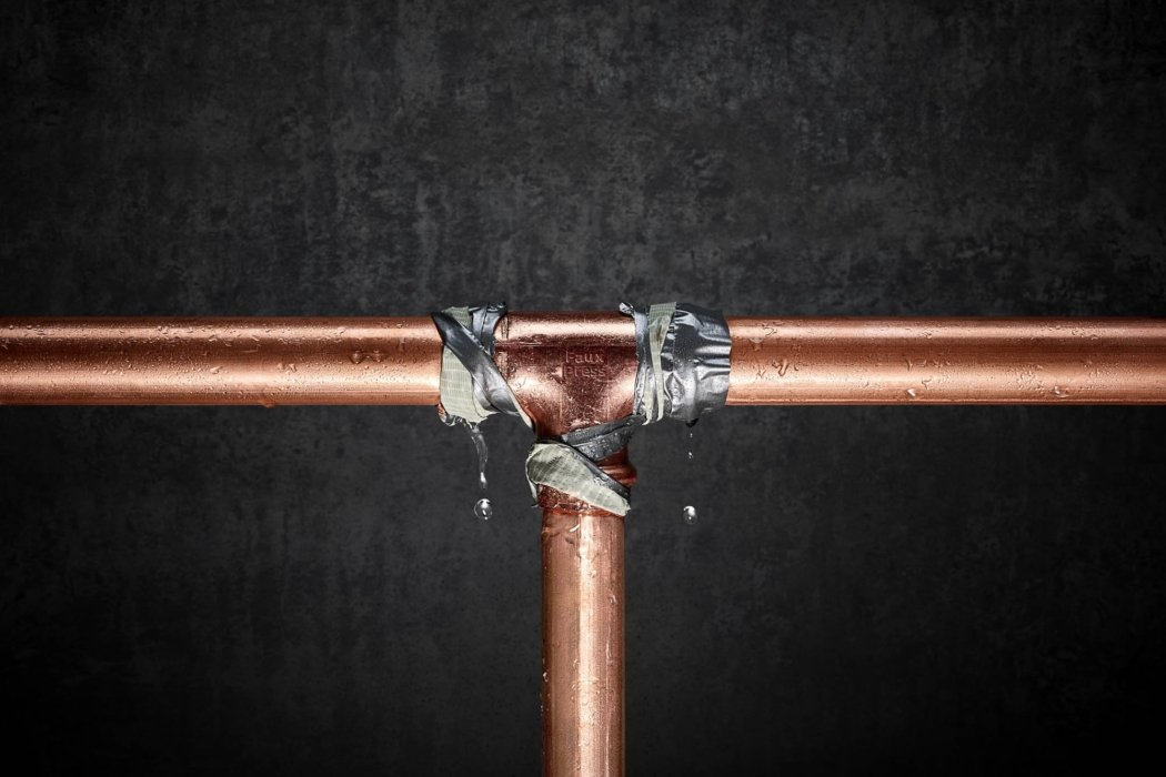 Liquid photography - a leaky copper t-joint pipe being sealed with duct tape