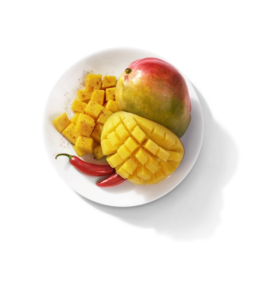 Spicy mangoes and peppers on white background