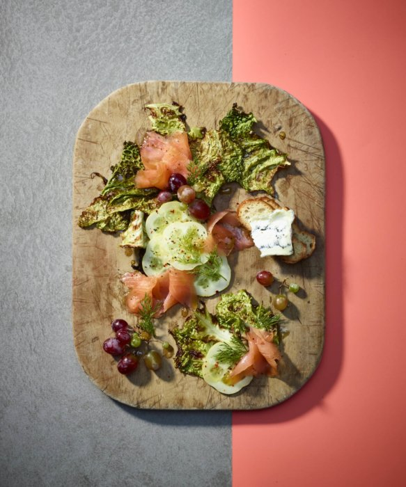 A charcuterie modern on pink and gray background. Smoked salmon cucumber