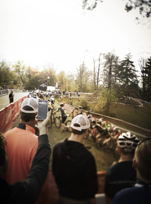 A crowd cheering on a pack of cyclocross riders