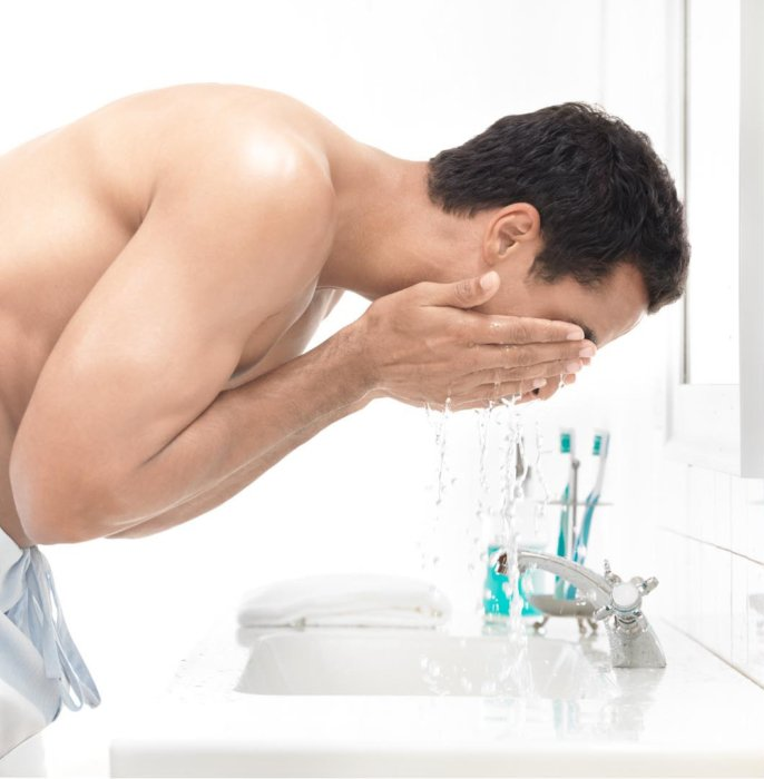 Beauty shot of a young man washing his face in a white bathroom