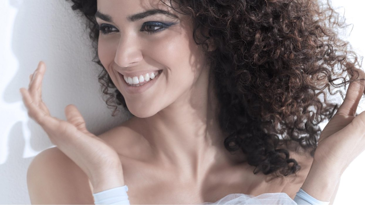 Beauty shot of a woman holding her hands up to the sides of her face with curly hair