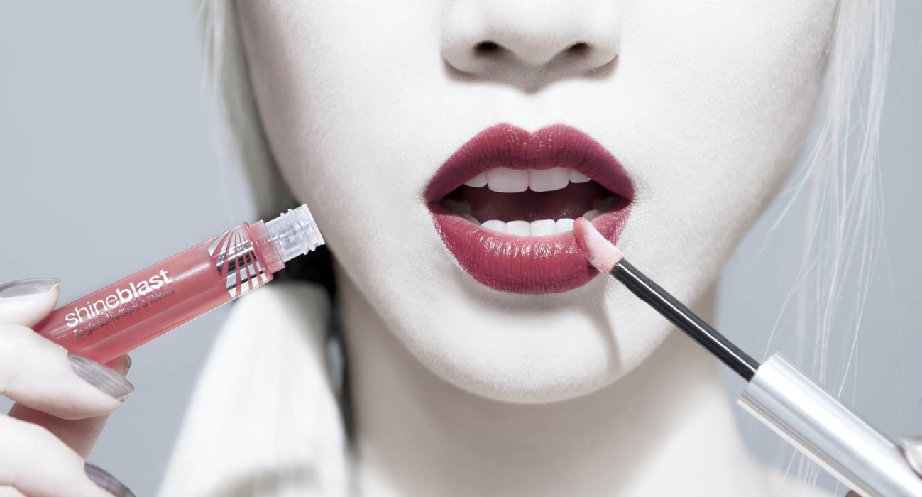 A beauty shot of a woman using shine blast lips