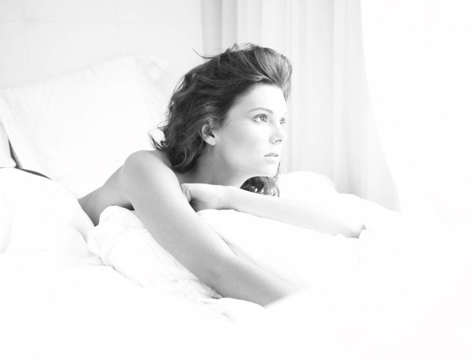 Beauty shot of a topless woman on some bedding black and white
