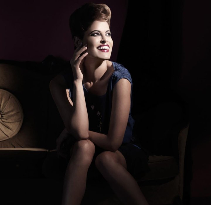 A fashion model wearing vintage style sitting and smiling.