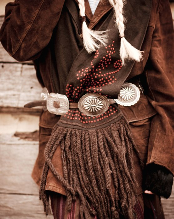 A fashion model wearing 1800's western clothes with metal belt buckles