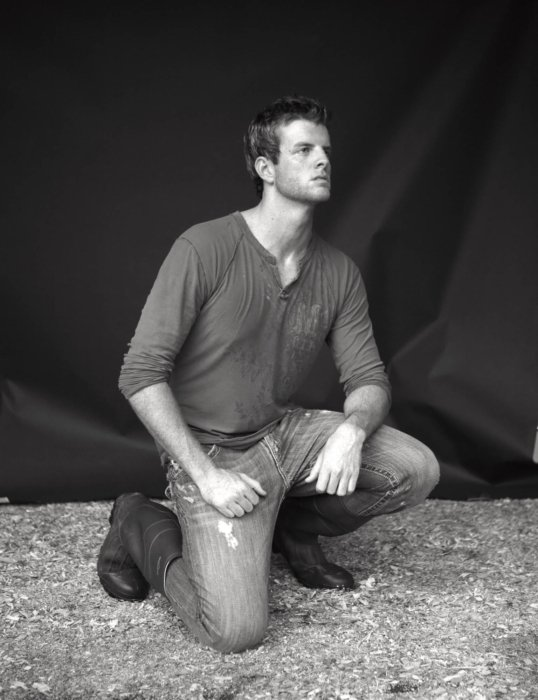 Fashion photo of a young man wearing rugged clothes while kneeling