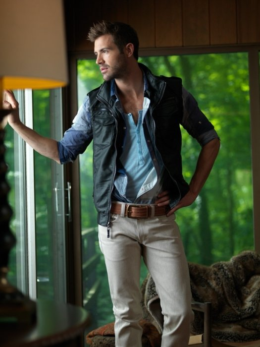 A dark image of model wearing shirt and vest looking out a window