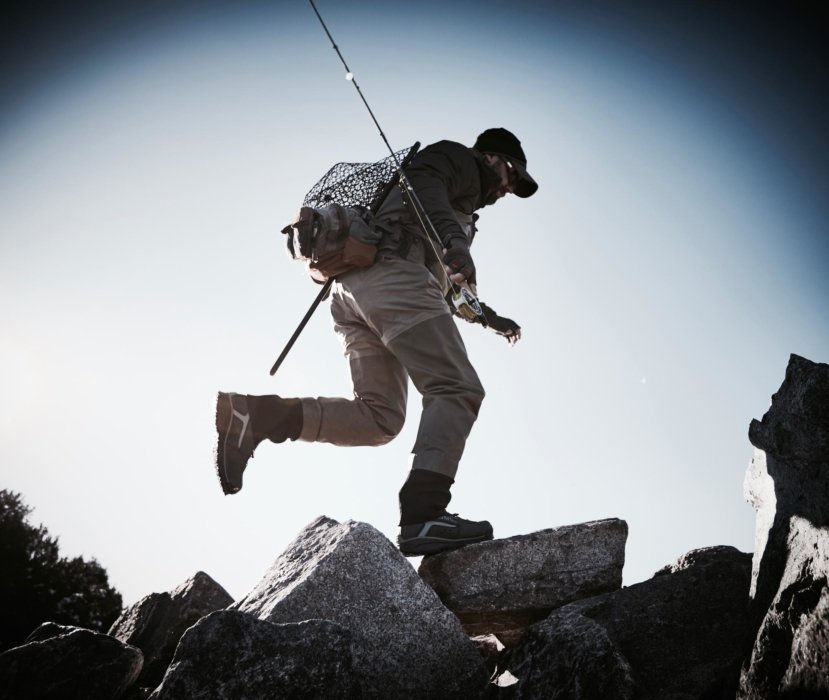 A fly fisherman running on some mountain rocks