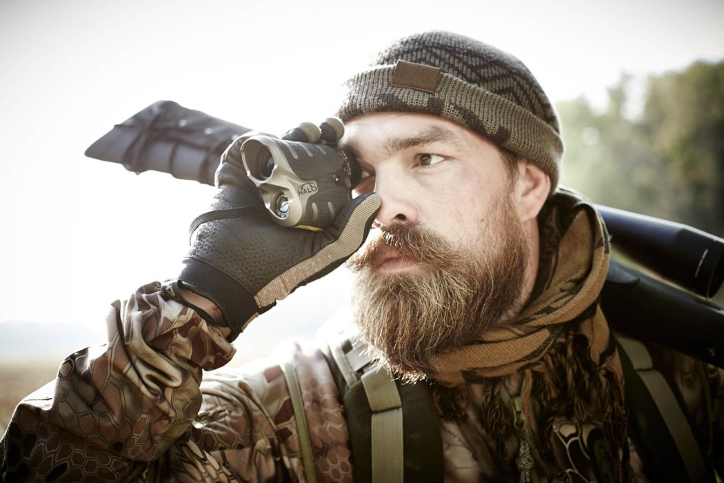 A rifle hunter using a rangefinder