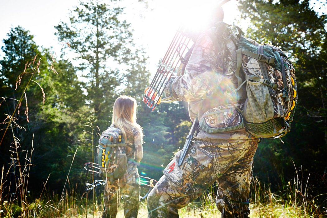 Two bow hunters in a sunny woodland clearing