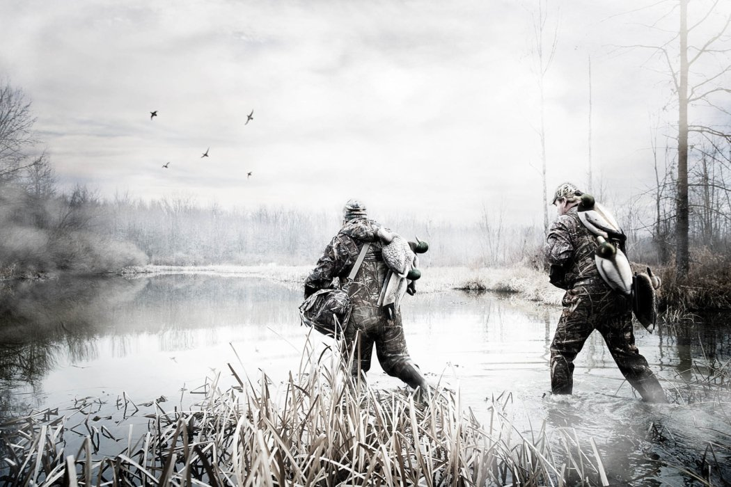 Two duck hunter wading in shallow winter pond