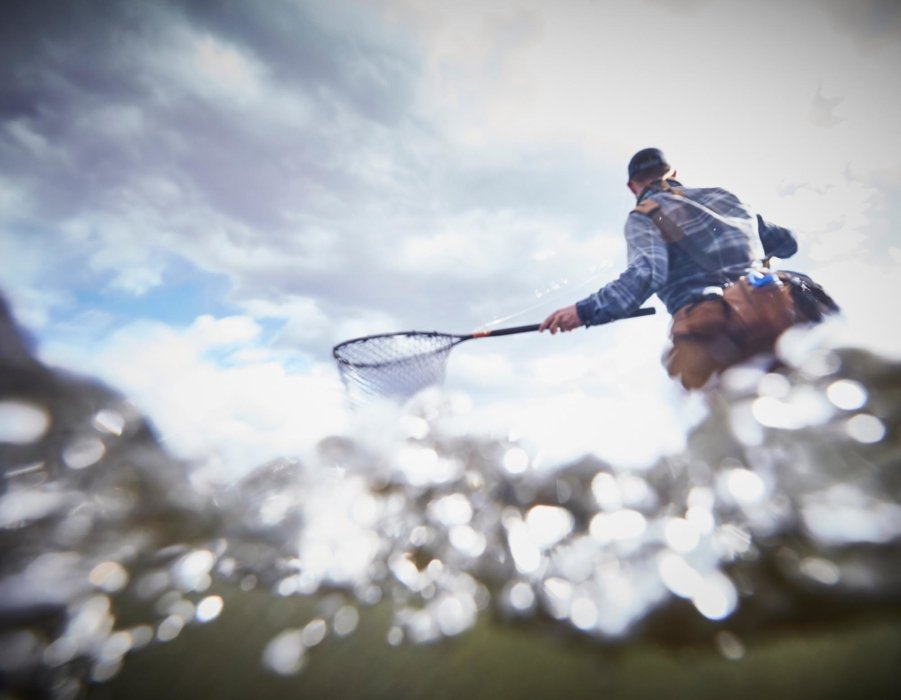 A fly fisherman with a net split shot