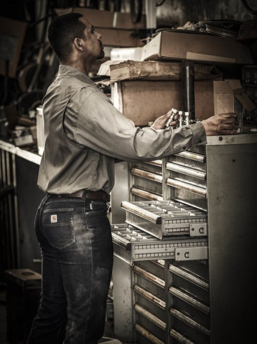 A man organizing materials while wearing tough work apparel