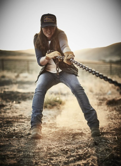 A rancher pulling on a heavy chain