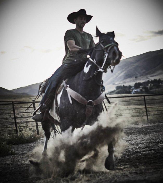 A rancher riding a horse kicking up dirt
