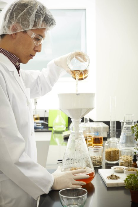 A male lab worker with a large funnel mixing amber and red liquids