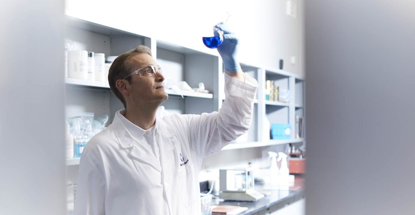 A male lab worker holding up a blue liquid filled beaker