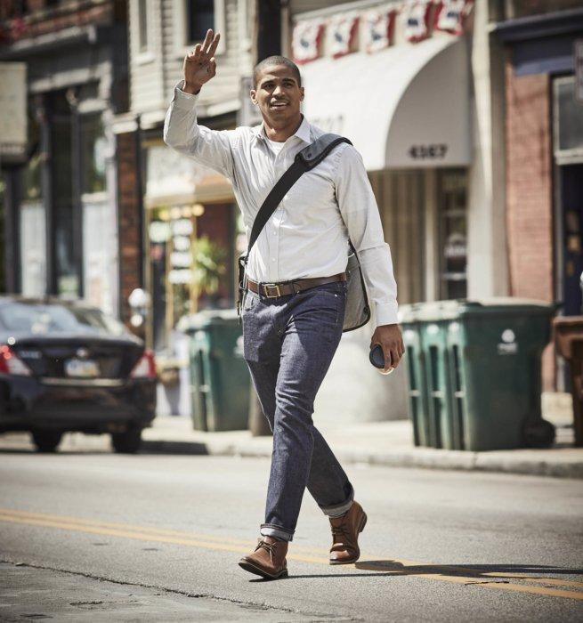 A young man walking across a street waving down a friend