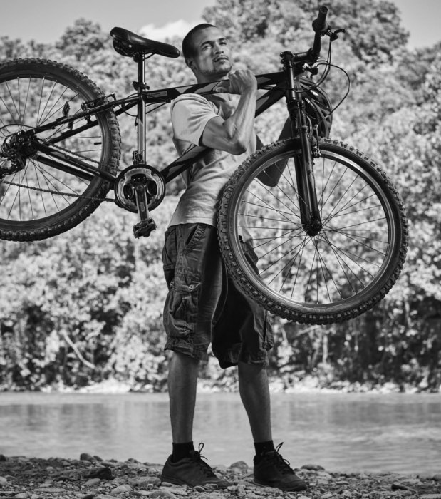 A young man carrying a bike by a river
