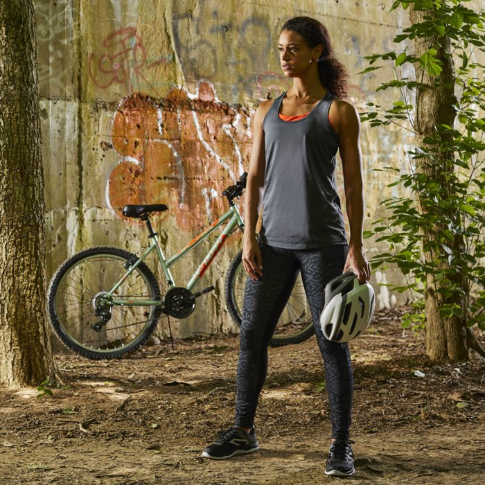 A young athletic woman standing by her bike under a bridge