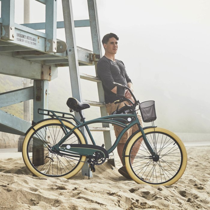 A guy next to a vintage style bike at a foggy beach