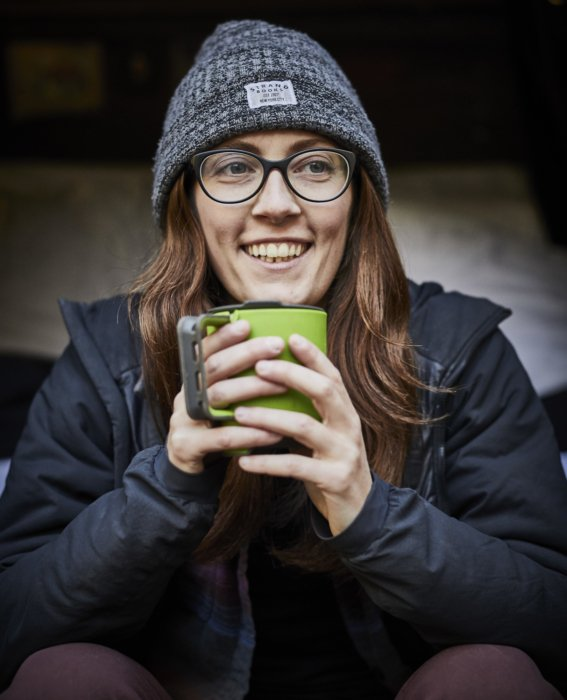 A portrait of young female rock climber with a cup of coffee