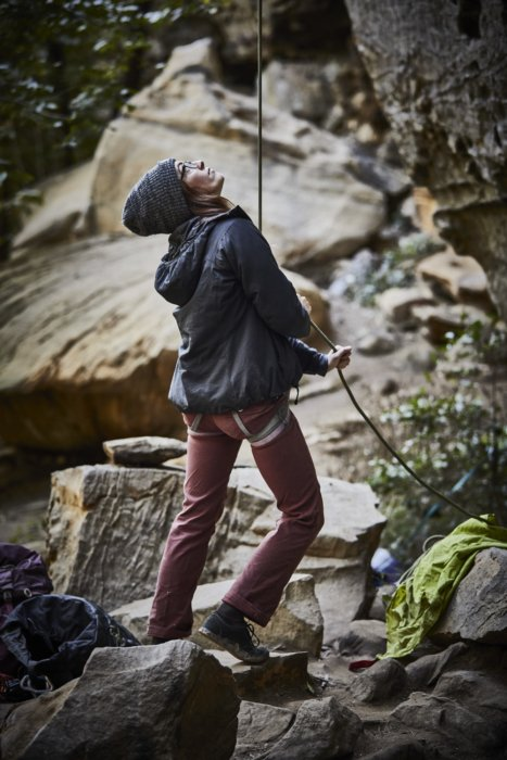 A female rock climber with rope spotting a climber