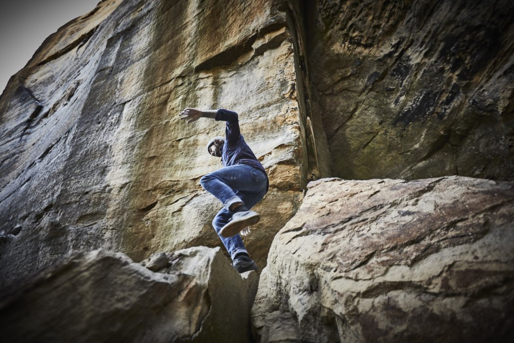 A male rock climber jumping from a large rock