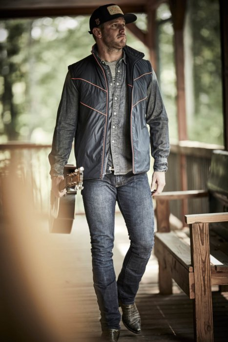 A famous country star walking with his guitar - rural cloth