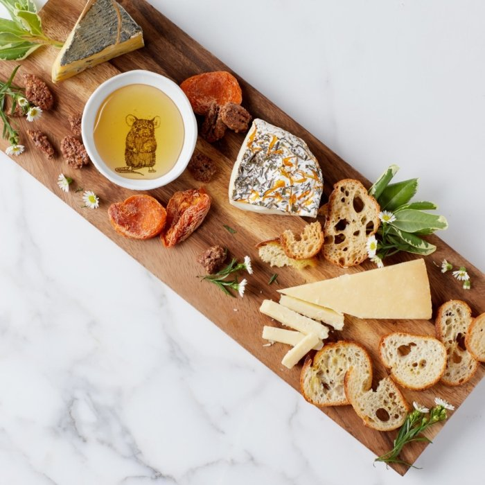 A spread of cheese, bread, and dried fruit featuring a plate with oil