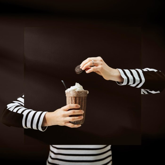 Surreal chocolate ice cream milkshake on a dark brown background