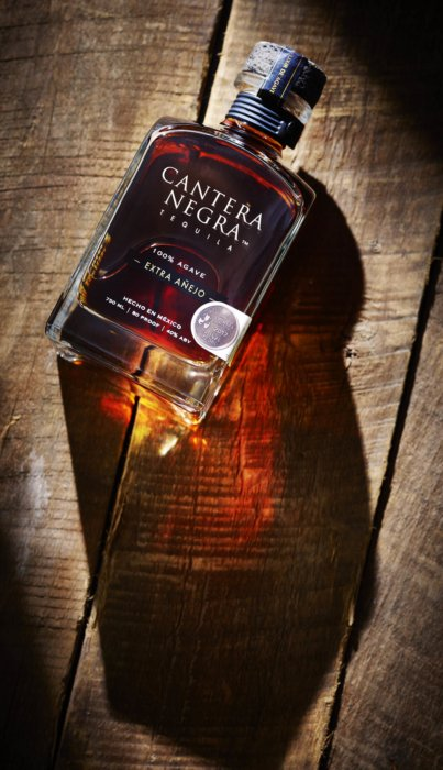Cantera Negra Tequila bottle on wood with dramatic light