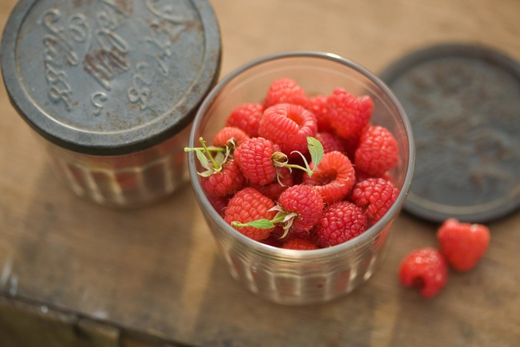 Raw raspberries in a glass jar